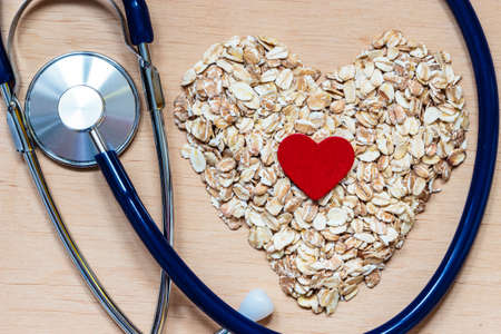 Foto für Dieting healthcare concept. Oat cereal heart shaped, stethoscope on wooden surface. Healthy food for lowering cholesterol, protect heart. - Lizenzfreies Bild