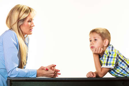 Photo pour Parenthood  domestic life and children upbringing. Mother talking with son little sad boy isolated on white background - image libre de droit