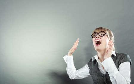 Business woman screaming looking upward in full fear wide open mouth grey wall background.