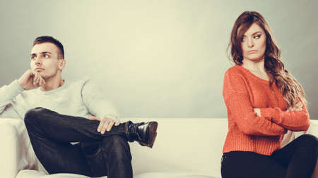 Photo pour Bad relationship concept. Man and woman in disagreement. Young couple after quarrel sitting on sofa - image libre de droit