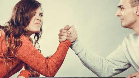 Photo pour Partnership relationship concept. Girlfriend confronts his boyfriend. Woman and man arm wrestling challenge between young couple - image libre de droit