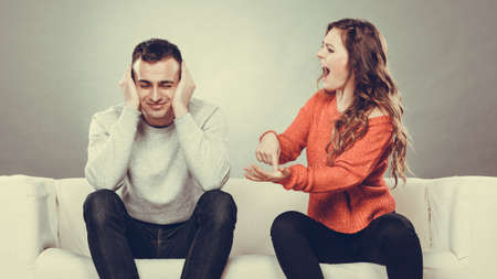 couple having argument - conflict, bad relationships. Angry fury woman screaming man closing his ears.