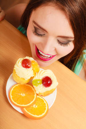 Woman hidden behind table sneaking and looking at delicious cake with sweet cream and fruits on top. Appetite and gluttony concept.