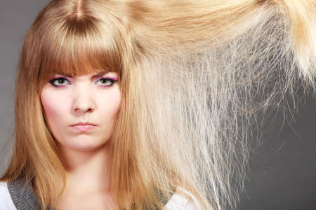 Photo pour Haircare. Blonde woman with her damaged dry hair angry face expression gray background - image libre de droit