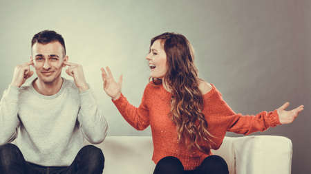 Photo pour couple having argument - conflict, bad relationships. Angry fury woman screaming man closing his ears. - image libre de droit