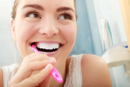 Photo pour Young woman brushing cleaning teeth. Girl with toothbrush in bathroom. Oral hygiene. - image libre de droit