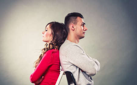 Photo pour Bad relationship concept. Man and woman in disagreement. Young couple after quarrel sitting on chairs back to back - image libre de droit
