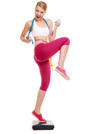 Slimming and weight loss success. Happy young woman girl measuring with tape measures on weighing scale clenching fists. Healthy lifestyle concept. Isolated on white.