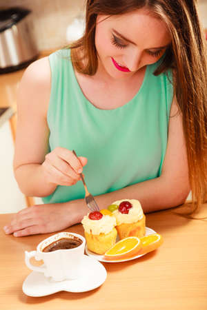 Woman with cup of coffee forking delicious gourmet sweet cream cake cupcake and orange. Glutton girl sitting in kitchen with hot beverage having breakfast. Appetite and gluttony concept.