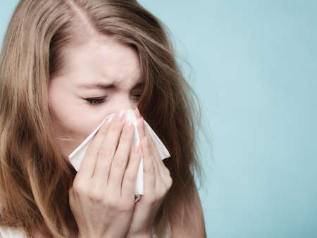 Foto de Flu cold or allergy symptom. Sick woman girl sneezing in tissue on blue. Health care. - Imagen libre de derechos