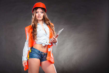 Photo for Sexy alluring woman structural engineer wearing helmet holding tablet computer. Strong girl feminist working in man profession. Independent female. - Royalty Free Image