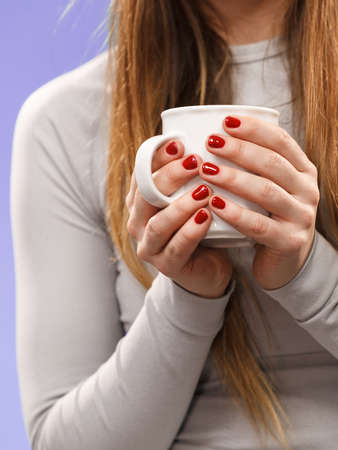 Photo pour Woman in winter gray sports thermal underwear for skiing training holds mug with tea or coffee warming herself studio shot on violet. - image libre de droit