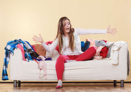 Photo pour Woman sitting on sofa couch in messy room. Girl surrounded by stack of clothes. Disorder and mess at home. - image libre de droit