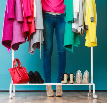 Foto per Closeup of woman choosing clothes to wear in wardrobe. Girl customer shopping in mall shop. Fashion clothing sale concept. - Immagine Royalty Free