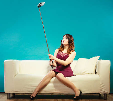 Photo pour Technology internet and happiness concept. Young woman funny girl taking self picture selfie with smartphone camera on stick while sitting on sofa at home - image libre de droit
