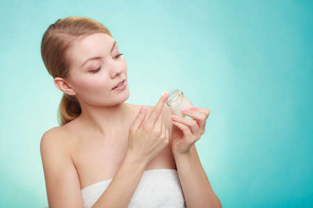 Beauty treatment. Woman applying moisturizing cream on face, holding jar with skin care product, studio shot on green blue background