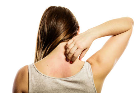 Photo pour Health problem. Young woman scratching her itchy back with allergy rash isolated on white - image libre de droit