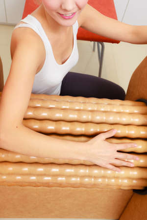 Skincare, bodycare, wellness concept. Woman getting rid of arms cellulite on big roll machine. Healthy massage treatment in spa