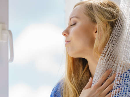 Photo pour Happy woman with long blonde hair sitting on windowsill and relaxing, meditate or thinking holding white lace curtain. - image libre de droit