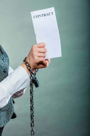Foto de Business concept. Serious woman businesswoman with chained hands holding contract, side view grungy background - Imagen libre de derechos