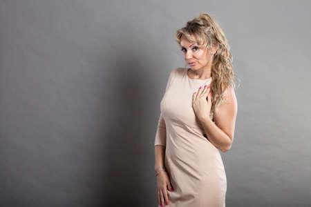Foto de Fashion, beauty, clothing, people concept. Picture with space and woman. Lady has beige dress. - Imagen libre de derechos