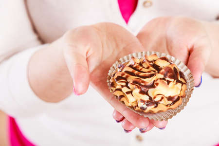 Delicious tasty sweet cake cupcake in human hands. Gluttony concept.