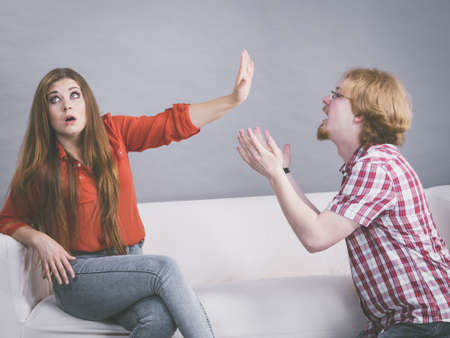 Photo pour Man begging woman who is sitting on sofa for forgiveness. Couple after fight or argue. Female showing speak to hand - image libre de droit