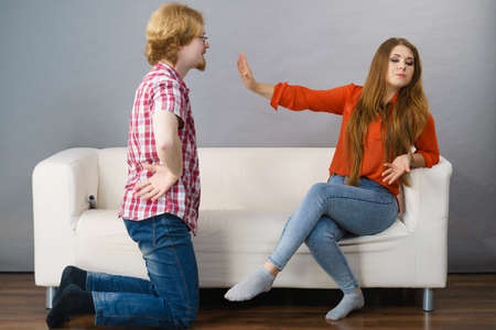 Photo for Man begging woman who is sitting on sofa for forgiveness. Couple after fight or argue. Female showing speak to hand - Royalty Free Image