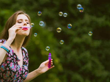 Foto de Happiness and carefree concept. Young woman having fun blowing soap bubbles outdoor in park - Imagen libre de derechos