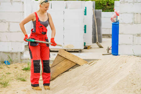 Photo pour Woman working hard on construction site, using shovel digging sand soil. Partially built new home early stage. Industry. - image libre de droit