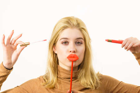 Photo pour Young adult woman applying lipstick or lip gloss, getting her make up done holding fake lips on stick - image libre de droit