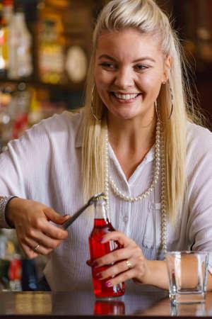 Photo pour Woman working at the bar counter, holding red bottle lemonade - image libre de droit