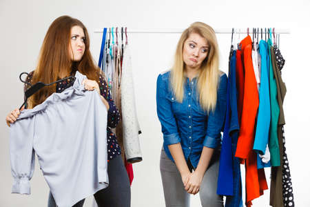 Photo pour Two funny women having argue during shopping about piece of clothing. Sales madness, blonde girl being sad - image libre de droit