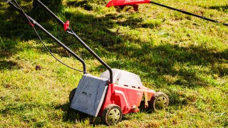 Foto de Gardening, garden service. Old lawn mower cutting green grass in backyard. Mowing field with lawnmower in sunny day. - Imagen libre de derechos