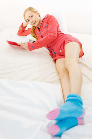 Photo for Girl lying in bed reading book. Young blonde female wearing red dotted pajamas blue warm socks relaxing at home on mattress. - Royalty Free Image
