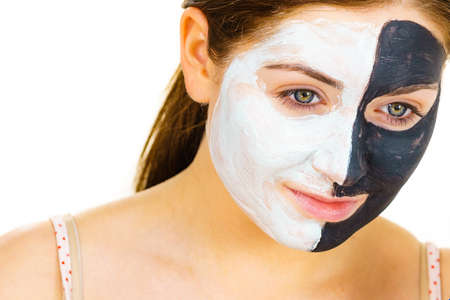 Photo pour Woman with clay carbo black mask on half face applying white mud to clean skin. Girl taking care of oily complexion. Beauty procedures. Skincare. - image libre de droit