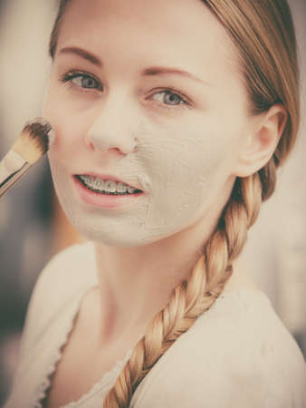 Foto de Skincare. Young woman applying with brush grey clay mud mask to her face. Female taking care of skin condition. Spa beauty treatment. - Imagen libre de derechos