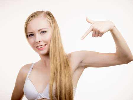 Foto de Young long hair blonde woman small boobs wearing bra, on white. Female breast in lingerie. Bosom, brafitting and underwear concept. - Imagen libre de derechos