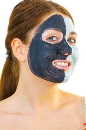 Photo pour Woman with clay carbo black mask on half face and white mud on second half. Girl taking care of oily complexion. Beauty procedures. Skincare. - image libre de droit