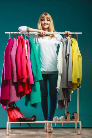 Photo pour Happy smiling pretty woman choosing clothes to wear in wardrobe. Gorgeous young girl customer shopping in mall shop. Fashion clothing sale concept. - image libre de droit