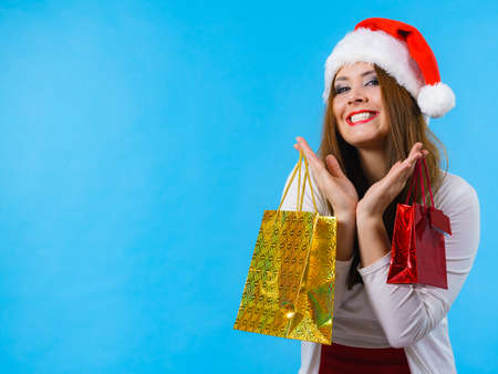 Photo for Young brunette woman is happy to give Christmas gifts. Female wearing santa claus hat holding presents festive gift bags, on blue - Royalty Free Image
