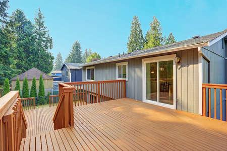 Photo pour Empty upper level deck boasts redwood railings overlooking the lower level deck. - image libre de droit