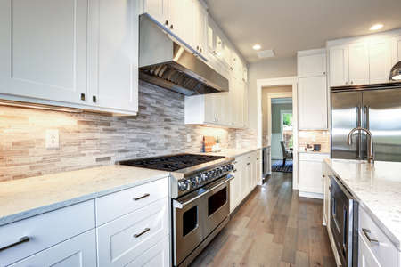 Foto de Amazing white kitchen design with white shaker cabinets paired with  white and gray marble counters, large White kitchen peninsula and high-end stainless steel appliances. - Imagen libre de derechos