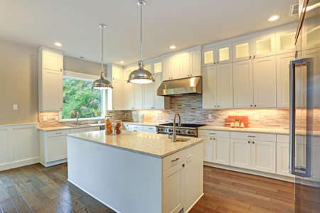 Photo pour Amazing white kitchen design with white shaker cabinets paired with  white and gray marble counters, large White kitchen peninsula and high-end stainless steel appliances. - image libre de droit