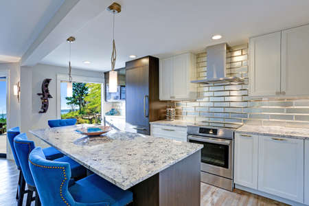 Photo pour Well appointed kitchen features a large kitchen island topped with a gray quartzite countertop and flanked by blue tufted dining chairs with silver nailhead trim. - image libre de droit