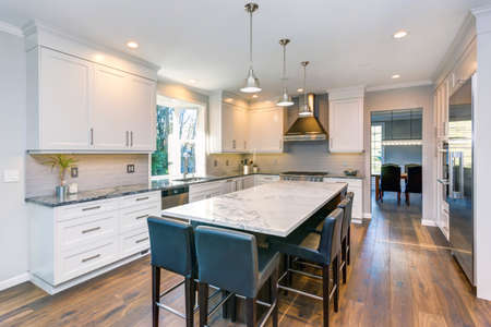 Photo pour Luxury home interior boasts Beautiful black and white kitchen with custom white shaker cabinets, endless marble topped kitchen island with black leather stools over wide planked hardwood floor. - image libre de droit