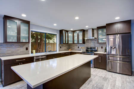 Photo pour Updated contemporary kitchen room interior with white counters and dark wood cabinets fitted with luxury stainless steel appliances.  - image libre de droit