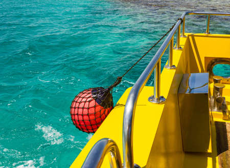 Part of fishing boat with red buoy against the sea
