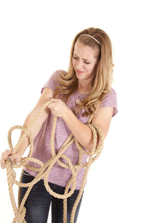 A girl all tangled up in a rope trying to get out.
