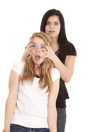a teenager with her hands on her friends face with a shocked expression on both of their faces.
